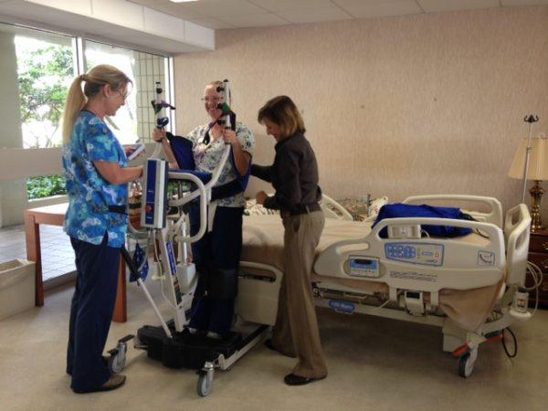 Nurses Melissa Magac (Nursing Supervisor) and Karen Novak demonstrate use of patient lift with Shelia Strahorn (Certified Nursing Assistant).