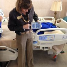 Karen Novak demonstrates use of the remote for operating the electric patient beds.